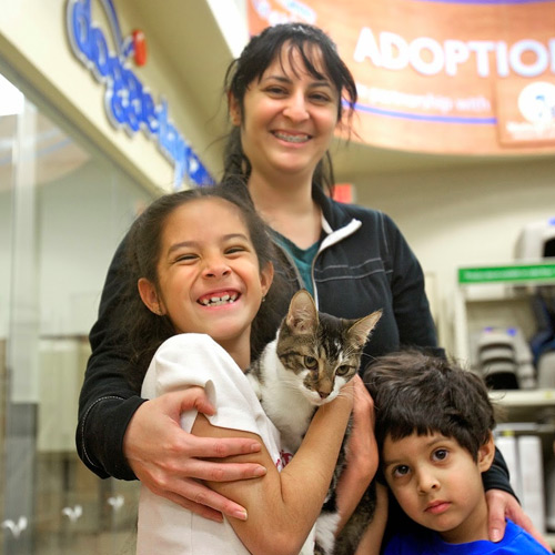 A mother poses with her young daughter and son after adopting a brown cat from The Everyday Adoption Center
