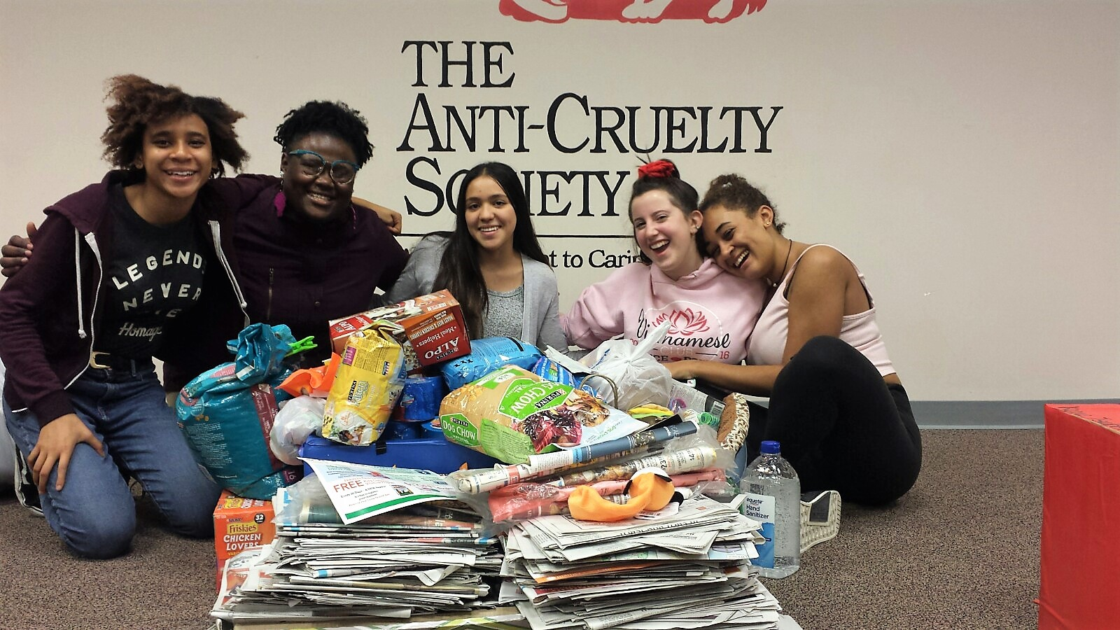 Group of students around donation of newspapers and pet food