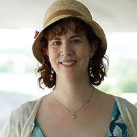 Woman in brown straw hat with brown hair wearing a blue dress