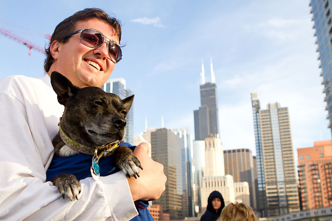 Man in black sunglasses on a boat holding small black dog with Chicago skyline in background