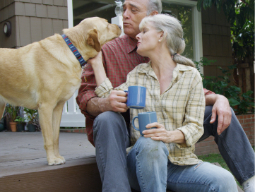 Older man and woman sitting on front porch steps with enjoying morning coffee while petting their golden lab.