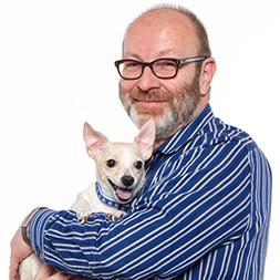 Man in blue and white striped shirt smiling holding small dog