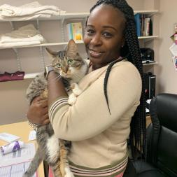 African American woman in tan sweater and pink shirt holding a brown and gray tabby cat