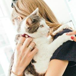 A young woman with long blonde hair in a black t-shirt holds a white cat on her shoulder