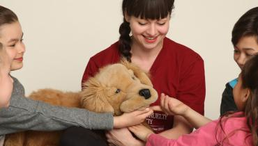 Woman surrounded by kids playing with puppet dog