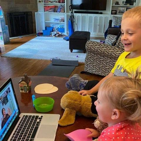 Two young children with stuffed animals looking a story time on a laptop computer