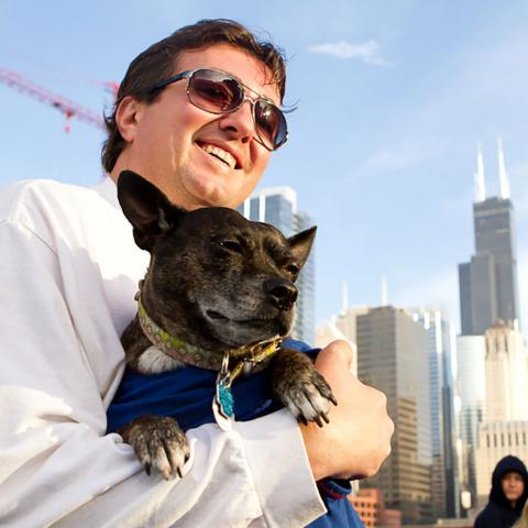 White man with brown hair wearing sunglasses holding small dog with Chicago skyline in background